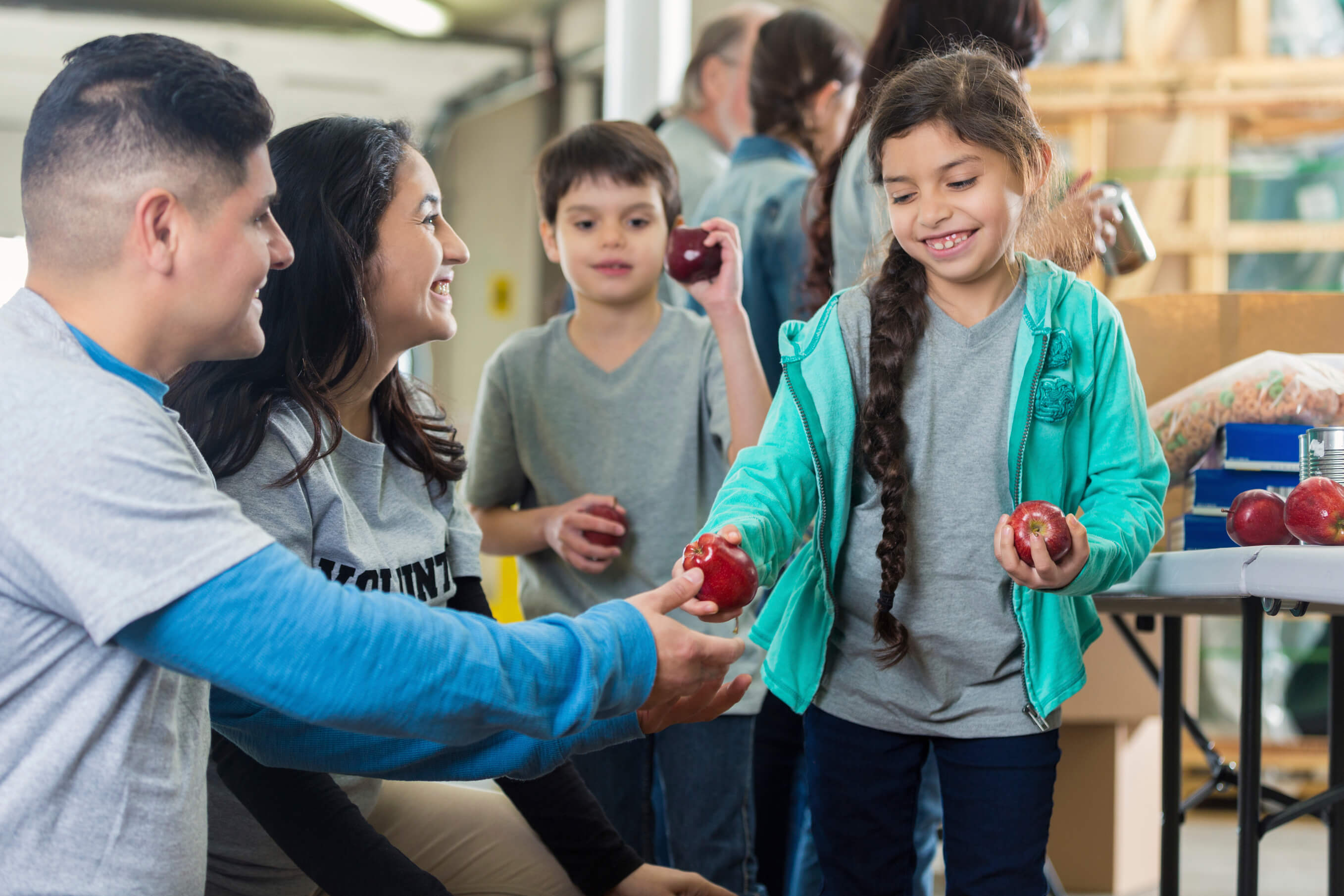 Mid adult Hispanic father and mother give their elementary age son and daughter apples in community food bank or soup kitchen. The children smile as they receive the apples. Volunteers are working in the background.